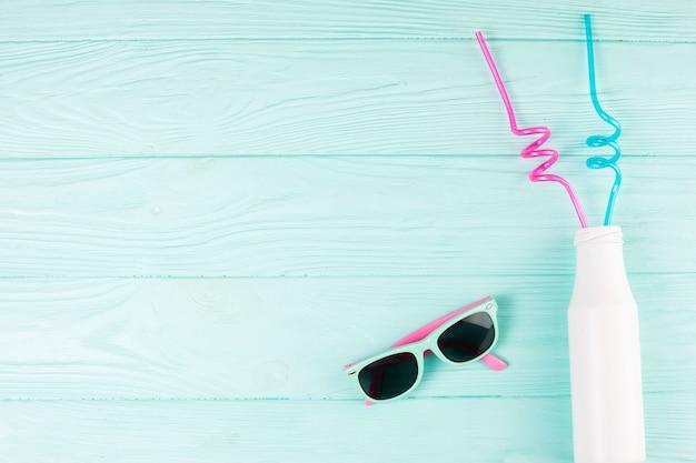 Sonnenbrille und flasche mit strohhalmen