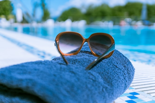 Sonnenbrille und handtuch in der nähe von schwimmbad