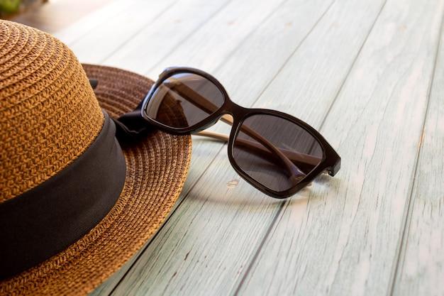 Sonnenbrille und hut auf holztisch selektiver fokus