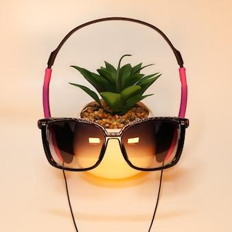 Sonnenbrille und kopfhörer in goldenem licht auf pflanze im topfruhekonzept und entspannung