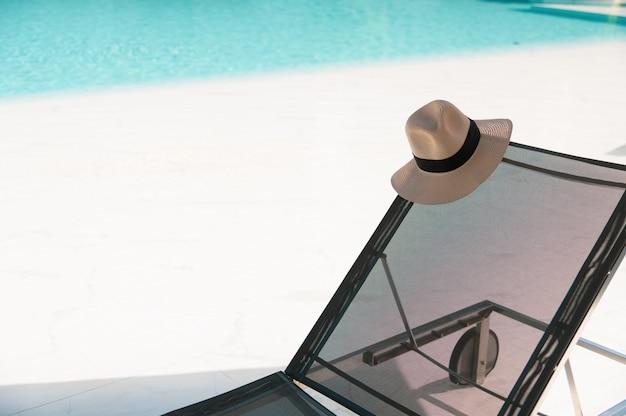 Sonnenbrille und strohhut auf dem strandbett
