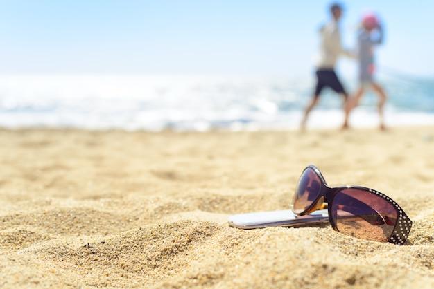 Sonnenbrille und telefon auf dem strand mit leuten auf hintergrund