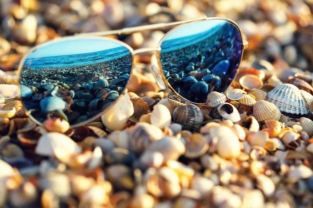Sonnenbrillen am strand mit meeresreflexion