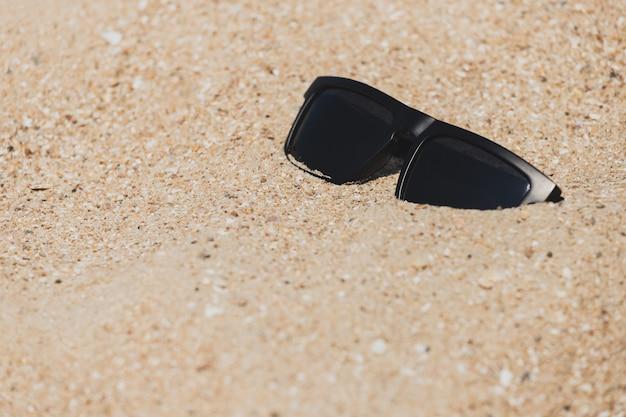Sonnenbrillen auf den sand gelegt