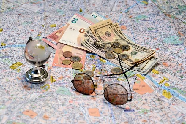 Sonnenbrillen, eine glaskugel und geld auf einem touristischen kartenhintergrund. tourismuskonzept.