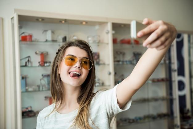 Sonnenbrillen machen mich frecher und edler hübsche kaukasische brünette, die selfie im optikerladen macht, während sie eine stilvolle gelbe brille anprobiert
