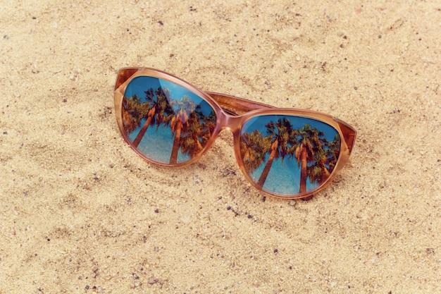 Sonnenbrillen mit palmenreflexion auf den gemischten medien des strandes