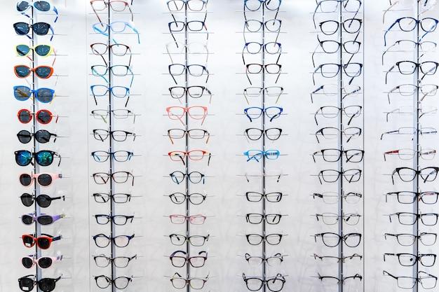 Sonnenbrillen und brillen in den ladenregalen. stehen sie mit brille im laden der optik.