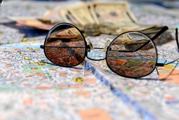 Sonnenbrillen und geld auf einem touristischen kartenhintergrund. tourismuskonzept.