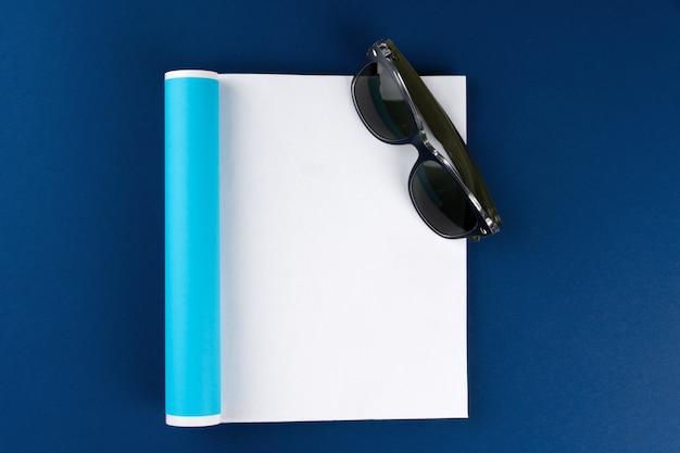 Sonnenbrillen und leere magazinseite auf klassischem blauem hintergrund, draufsicht