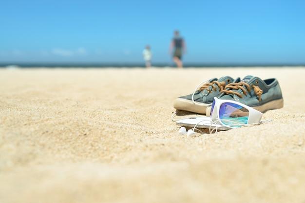 Sonnenbrillen und schuhe am strand mit menschen im hintergrund