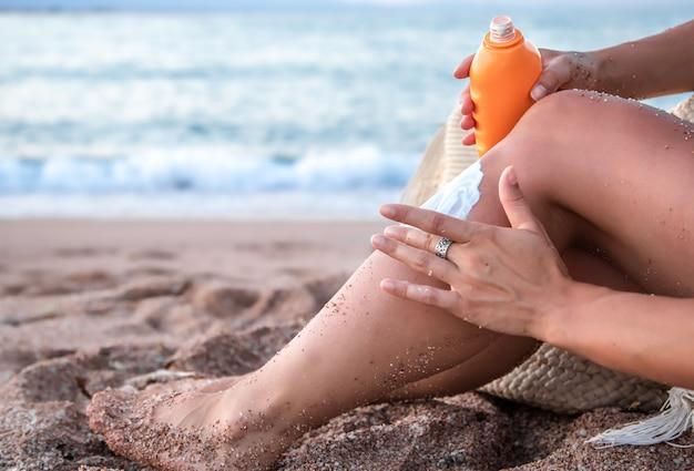 Sonnencreme auf weiblichen füßen am strand. körperteil. sonnenschutzkonzept.