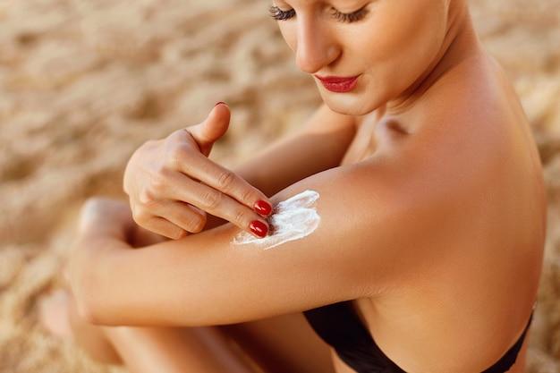 Sonnencreme. haut- und körperpflege. frau im bikini, die sonnenschutz-solar auf gebräunter schulter anwendet.