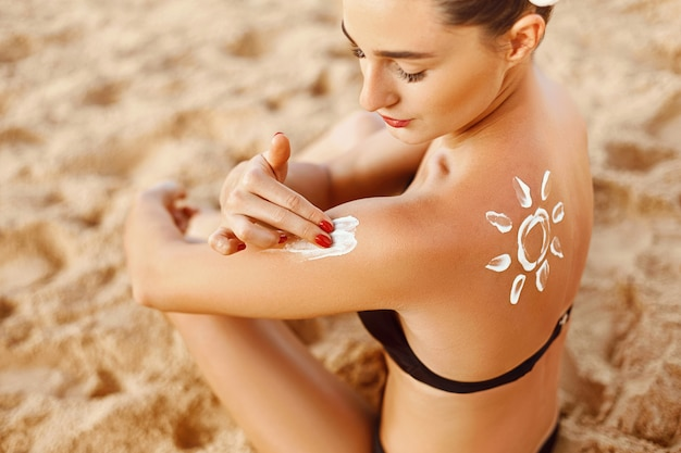 Sonnencreme. junge frau, die sonnenschutz-sonnencreme auf dem strand anwendet. sonnenform auf der schulter.