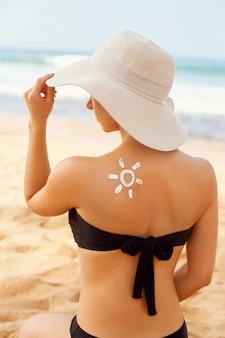Sonnencreme. schöne frau der sonnencreme, die auf gebräunter schulter in form der sonne anwendet.