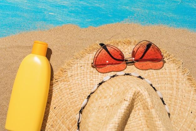 Sonnencreme, strohhut und sonnenbrille auf sand, draufsicht