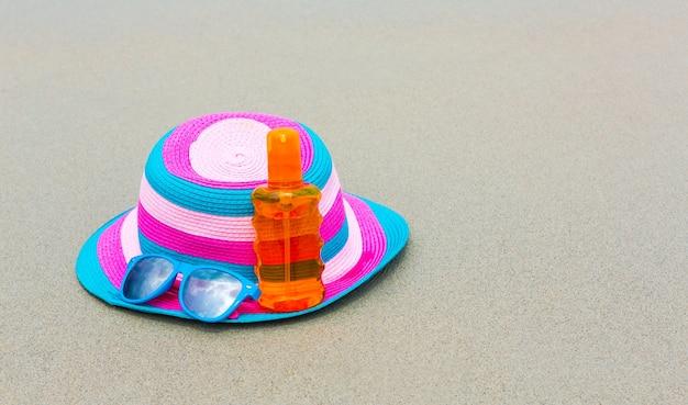 Sonnencreme und eine dunkle brille mit hut am strand für summ