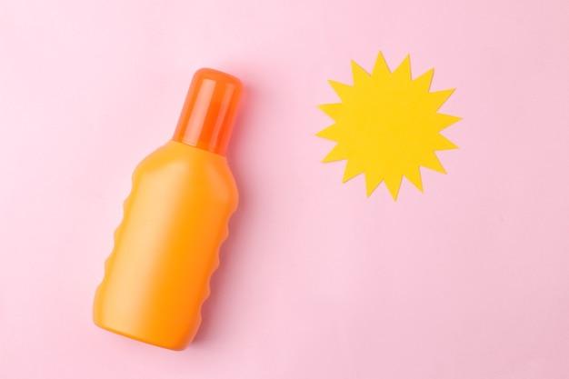 Sonnencreme und papiersonne. sommer. ferien. sonnenschutz. ansicht von oben.