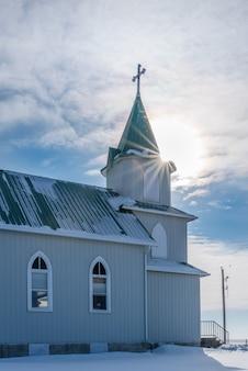 Sonnendurchbruch über der historischen lutherischen friedenskirche auf den prärien in saskatchewan, kanada