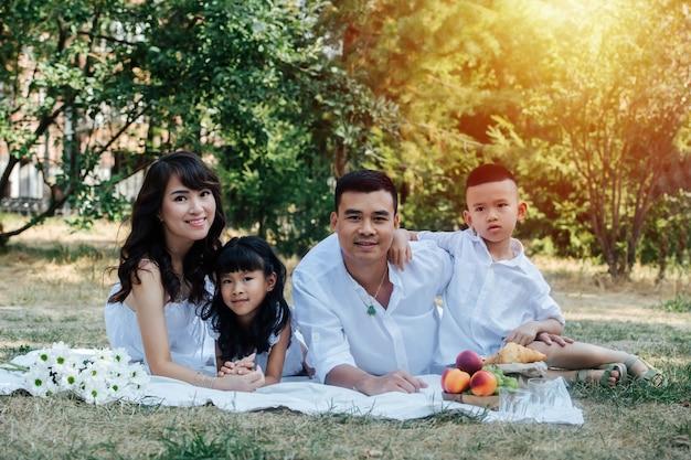 Sonnendurchflutetes porträt einer asiatischen familie in weißer kleidung, die ein picknick in einem park macht und die letzten warmen tage des frühen herbstes genießt. eltern und ihre kinder in einem baumschatten.