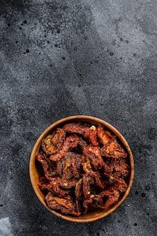 Sonnengetrocknete tomaten in holzschale. schwarzer, dunkler hintergrund
