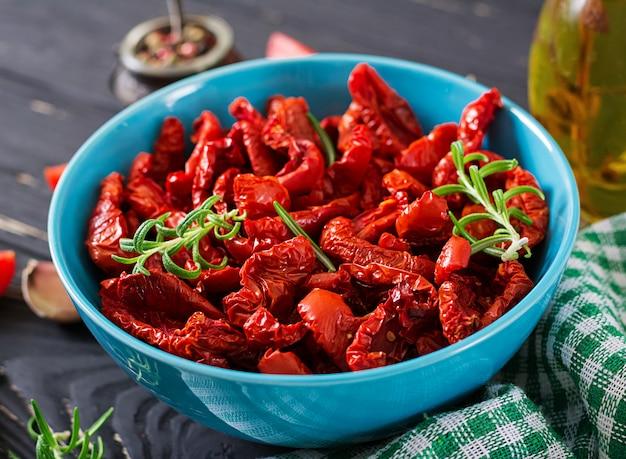 Sonnengetrocknete tomaten mit kräutern und knoblauch in der schüssel auf holztisch. italienisches essen.