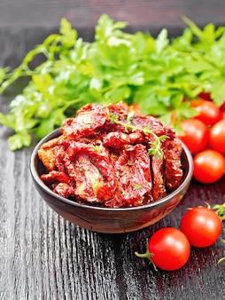 Sonnengetrocknete tomaten mit thymian und basilikum in einer schüssel, frische kleine tomaten, petersilie auf holzbretthintergrund