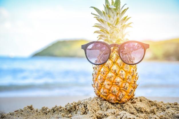 Sonnenglas ist auf ananas am strandseeansichthintergrund, sommerferienkonzept