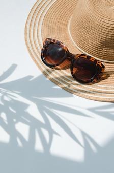 Sonnenhut und sonnenbrille mit palmenschatten