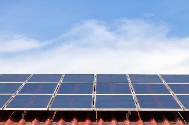 Sonnenkollektor- und sonnenenergieplatte auf blauem himmel und sonnenlicht des roten dachs