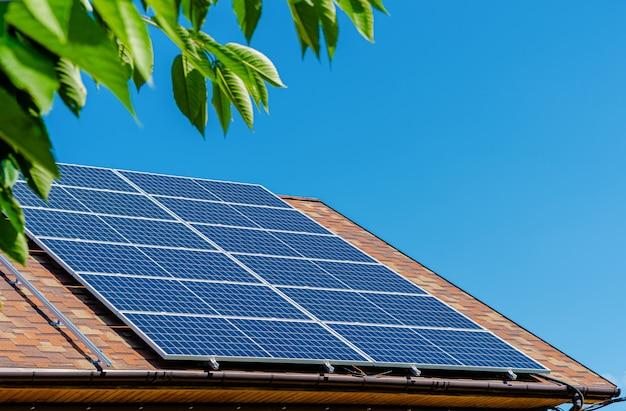 Sonnenkollektoren auf dem dach. konzept für grüne energie und geld sparen.