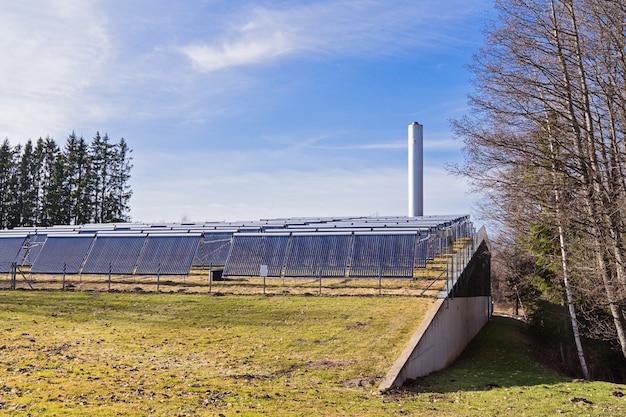 Sonnenkollektoren auf dem feld mit einem heizkesselraum