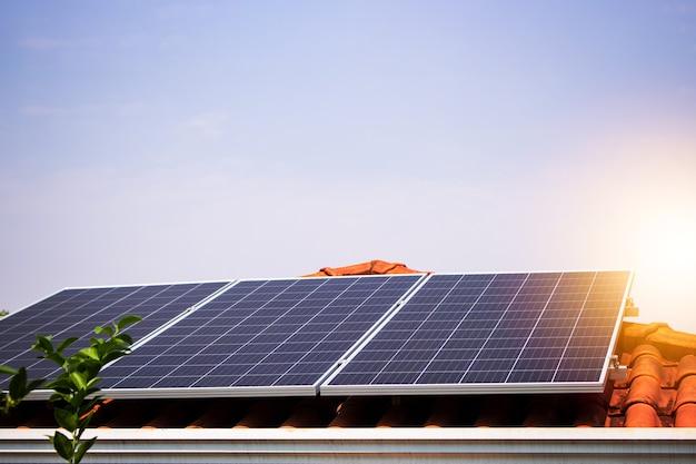 Sonnenkollektoren auf dem roten dach an einem sonnigen und bewölkten tag. foto einer photovoltaikanlage.