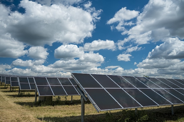 Sonnenkollektoren für erneuerbare energien auf dem feld unter dem wolkenreichen himmel