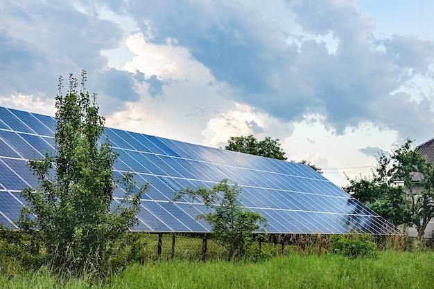 Sonnenkollektoren im garten. solarkraftwerk zwischen bäumen und büschen.