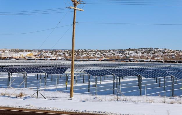 Sonnenkollektoren in der winteransicht des schnees bedeckten sonnenkollektorpark, photovoltaik-kraftwerk