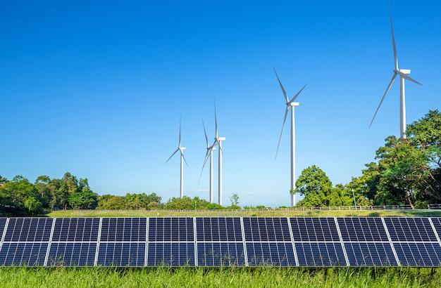 Sonnenkollektoren mit windkraftanlagen gegen mountanis landschaft gegen blauen himmel mit wolken.
