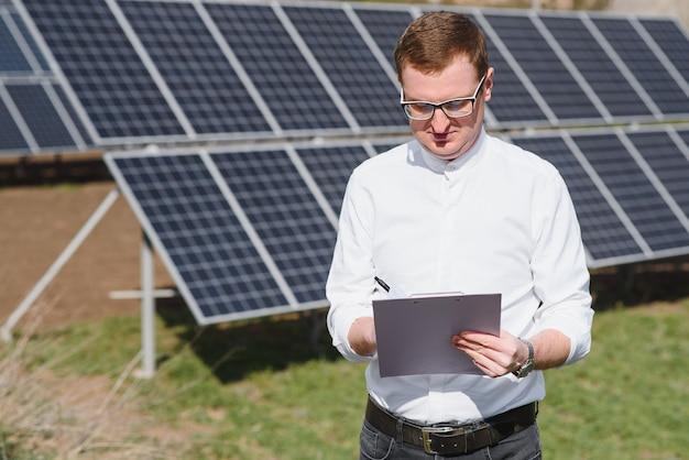 Sonnenkollektoren und ein mann, der in der nähe von sonnenkollektoren steht
