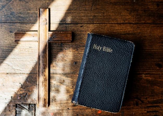 Sonnenlicht auf einer bibel und einem hölzernen kreuz