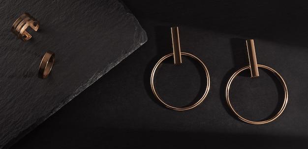 Sonnenlicht auf goldenem ohrringpaar und ringe auf schwarzem steinhintergrund. draufsicht des modernen goldenen zubehörs auf schwarzem steinhintergrund.