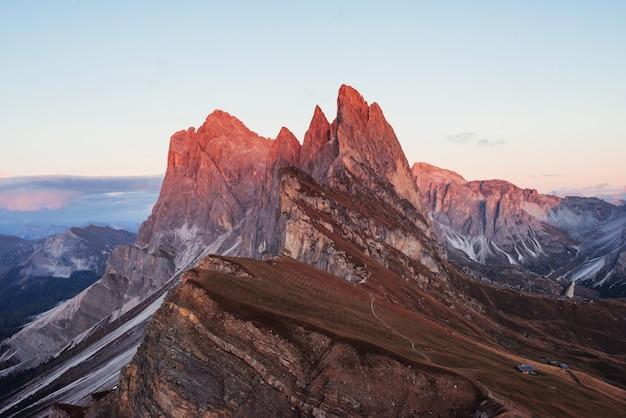 Sonnenlicht oben. landschaft von hügeln und klippen zur tageszeit. kleine gebäude auf der rechten seite.