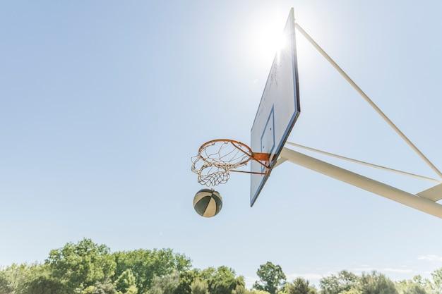 Sonnenlicht über dem basketballkorb gegen blauen klaren himmel