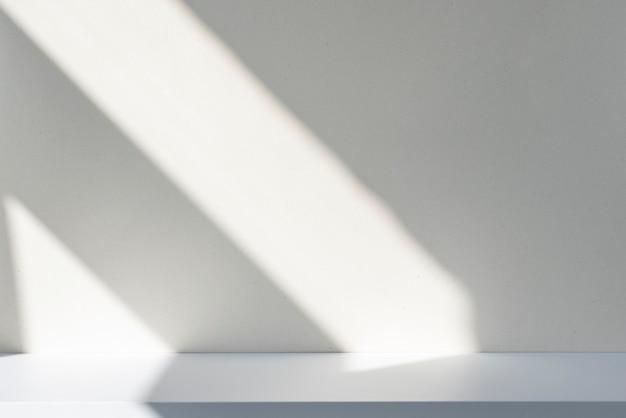 Sonnenlicht und abstrakte schatten an der wand und am weißen schreibtisch. silhouette von linien auf leerer oberfläche, modell, platz für text.