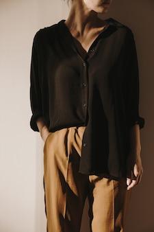 Sonnenlichtschattenreflexionen an der wand. schöne frau in schwarzem hemd und brauner hose bleibt an der wand
