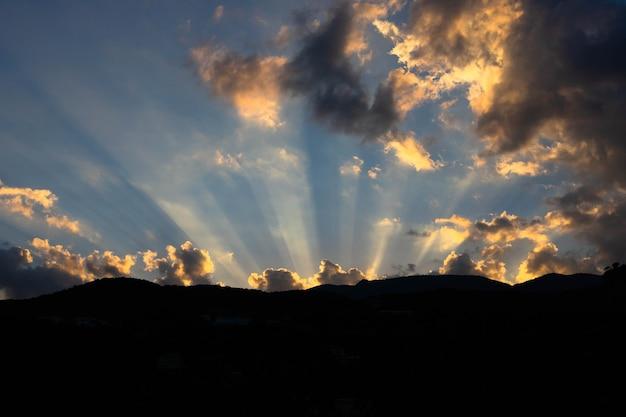 Sonnenlichtstrahlen, die durch dunkle wolken über den bergen scheinen. foto in hoher qualität