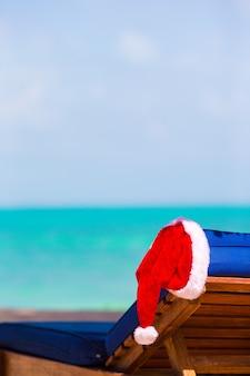 Sonnenliege mit santa hat am schönen tropischen strand mit weißem sand und türkiswasser.