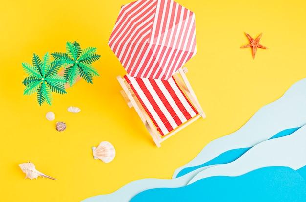 Sonnenliege, spielzeugpalmen, papiermeerwellen. sommerferien und strand, küstenferienkonzept