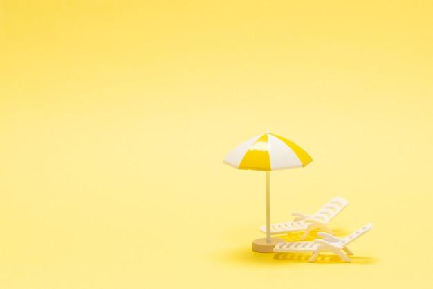 Sonnenliege und gelber regenschirm auf gelbem grund.