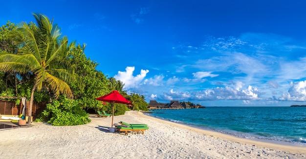 Sonnenliege und sonnenschirm am tropischen strand auf den malediven