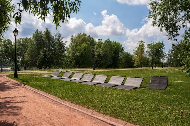 Sonnenliegen zum entspannen im park. grüne gassen und wege
